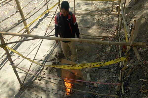 Pengunjung berusaha membakar daun jati kering pada titik semburan api dari perut bumi yang muncul di area tegalan di Dukuh Banyurip, Desa Bonagung, Kecamatan Tanon, Sragen, Kamis (5/9/2019). - JIBI/Muh Khodiq
