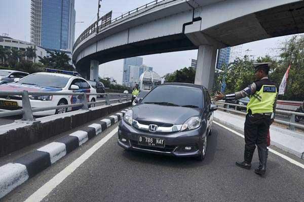 Petugas Ditlantas Polda Metro Jaya memberhentikan mobil berpelat nomor genap yang memasuki Jalan Gatot Soebroto, Jakarta - ANTARA/Hafidz Mubarak A