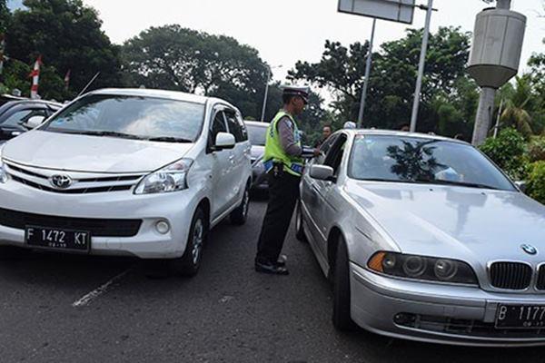 Polisi memberhentikan mobil berpelat nomor ganjil yang melintas pada tanggal genap di kawasan pembatasan lalu lintas ganjil-genap di sekitar Bundaran Senayan, Jakarta, Selasa (30/8). - Antara