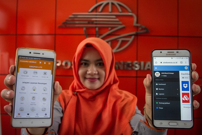 Karyawan PT. Pos Indonesia menunjukkan layanan aplikasi digital berbasis rekening Giro Pos Mobile (kiri) dan aplikasi Cas On Delivery Costumer to Costumer (COD C2C) (kanan) di Kantor Pos Besar, Solo, Jawa Tengah, Senin (2/9/2019). PT. Pos Indonesia melakukan inovasi terhadap produk yang sudah ada dengan menyesuaikan dalam bentuk digital untuk meningkatkan layanan dan memudahkan pelanggan menjangkau layanan Perusahaan. - ANTARA / Mohammad Ayudha