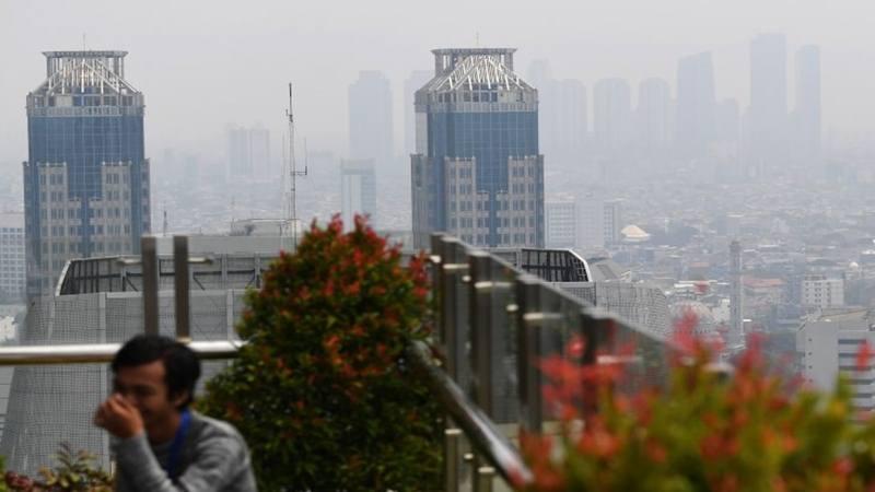 Warga beraktivitas dengan latar belakang suasana gedung bertingkat yang diselimuti asap polusi di Jakarta, Senin (29/7/2019). - Antara