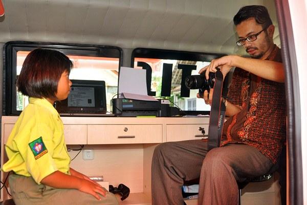 Petugas memotret seorang anak saat proses pembuatan Kartu Identitas Anak (KIA) di mobil Layanan Keliling Administrasi Kependudukan dan Pencatatan Sipil di Desa Muntung, Candiroto, Temanggung, Jawa Tengah, Rabu (26/4). - Antara/Anis Efizudin