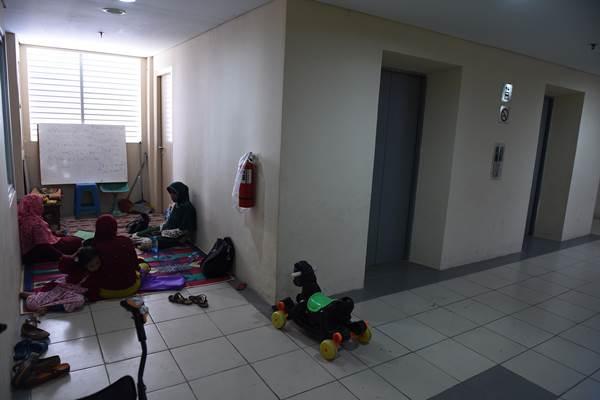 Warga duduk di depan kamarnya di Rumah Susun Jatinegara Barat, Jakarta, Jumat (14/8). - Antara