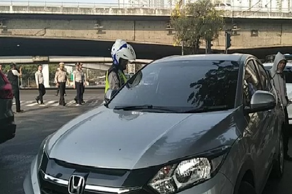 Anggota kepolisian satuan lalu lintas menilang pengendara mobil pribadi bernopol genap yang memasuki Jalan Tomang Raya, ruas jalan yang diterapkan perluasan ganjil-genap mulai Senin (9/9/2019). - Antara