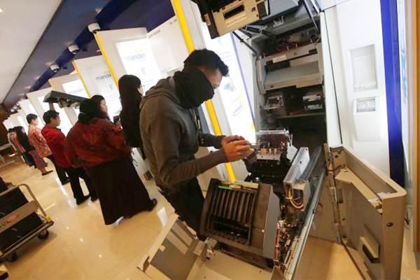 Petugas melakukan pemeriksaan rutin pada mesin ATM Bank Mandiri di Jakarta. - JIBI/Nurul Hidayat