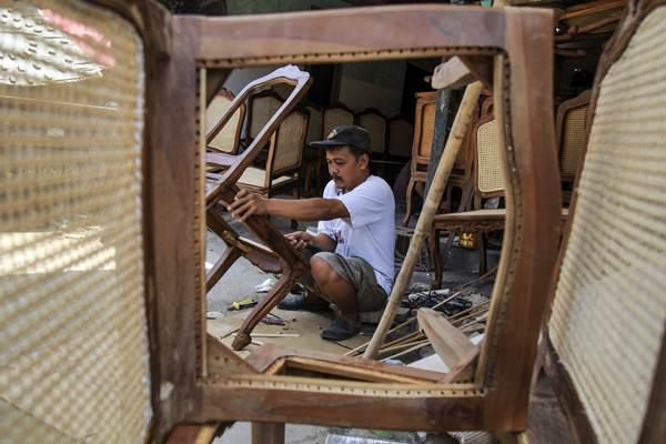 Pekerja menyelesaikan pembuatan kursi. - ANTARA/Maulana Surya