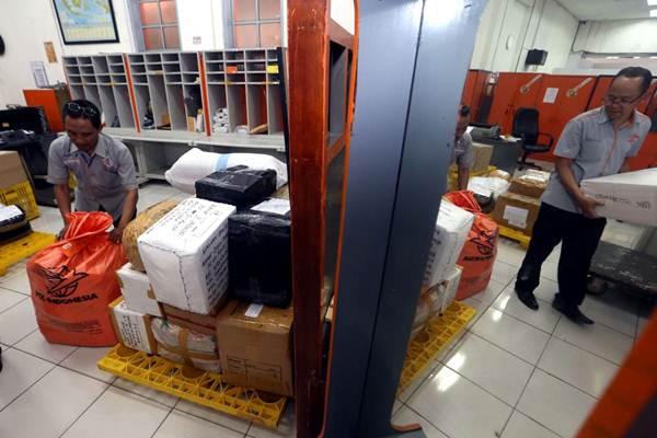 Pekerja mendata paket barang sebelum dialihkan ke pusat pemrosesan pos untuk dikirim ke tujuan, di Kantor Pos. - JIBI/Rachman