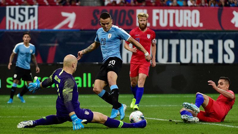 Kiper Timnas AS Brad Guzan (kedua kiri) berhasil membendung upaya penyerang Uruguay Jonathan Rodriguez (tengah) yang hendak menjebol gawangnya. Skor akhir 1 - 1. - Reuters