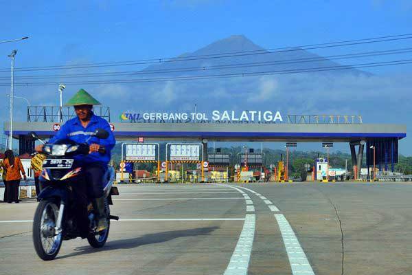 Warga melintas di sekitar gerbang jalan tol Salatiga yang berlatar belakang gunung Merbabu di Tingkir, Salatiga, Jawa Tengah, Kamis (8/6). - Antara/Aloysius Jarot Nugroho
