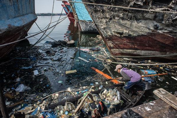 Pekerja membersihkan sampah yang terbawa arus di kawasan pesisir Muara Baru, Jakarta, Rabu (31/7/2019). Sampah-sampah yang sulit terurai seperti botol dan kemasan plastik masih menjadi salah satu masalah besar di Jakarta. - Antara/Aprillio Akbar.