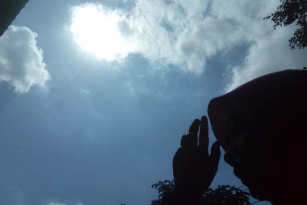 Warga menutup sinar matahari yang menyinari muka saat matahari bersinar terik di musim kemarau. - Harian Jogja/Nina Atmasari