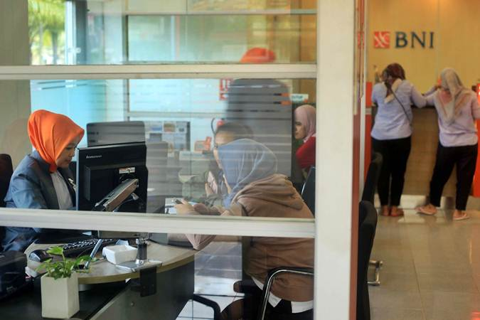 Karyawan melayani nasabah di kantor cabang Bank BNI, di Jakarta, Senin (25/2). - Bisnis/Nurul Hidayat