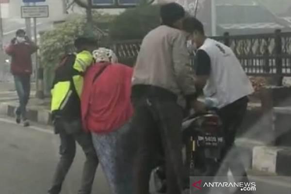 Warga menolong seorang perempuan di Dumai yang mendadak lemas di dekat perempatan Tugu PONTu, diduga akibat terpapar kabut asap. - ANTARA