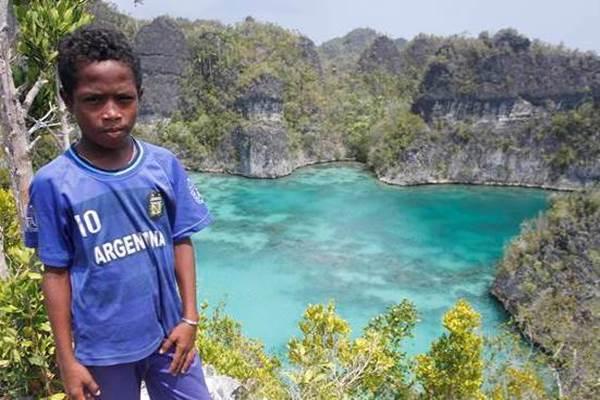 Seorang bocah berpose dengan latar belakang telaga bintang di Raja Ampat, Papua Barat - Antara