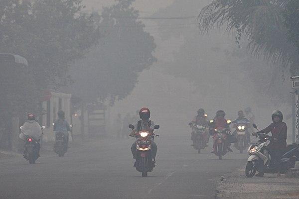 Warga berkendara menembus kabut asap - ANTARA/Syifa Yulinnas