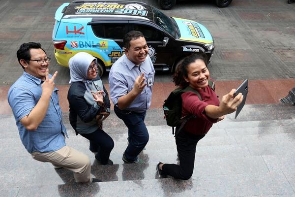 Head of Performance and Channel Management Group PT Bank Negara Indonesia (Persero) Tbk. Yudi Indra A (kedua kiri), Pengelola Service Management Region Palembang Natia Indriani (kedua kanan), Tim Jelajah Infrastruktur Sumatra 2019 Rivki Maulana (kiri) dan Ropesta Sitorus berswafoto di Palembang, Jumat (13/9/2019). BISNIS - Nurul Hidayat