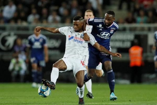 Ujung tombak Lyon Moussa Dembele (kiri depan) dibayangi bek Amiens Aurelien Chedjou. - Reuters/Gonzalo Fuentes