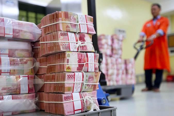 Karyawan menata uang rupiah - Bisnis/Abdullah Azzam