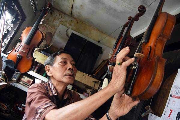 Markoem (84) perajin biola memeriksa salah satu biola produksinya di kawasan Kaliasin, Surabaya, Jawa Timur. - ANTARA/M Risyal Hidayat