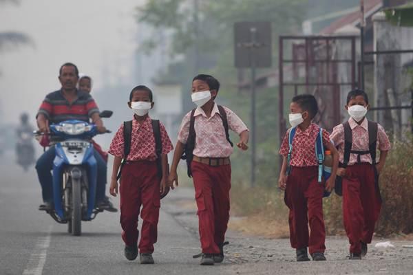 Sejumlah siswa memakai masker saat berjalan menuju ke sekolah mereka, di Desa Suak Raya, Johan Pahlawan, Aceh Barat, Aceh, Kamis (27/7). - ANTARA/Syifa Yulinnas