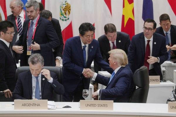 Perdana Menteri (PM) Jepang Shinzo Abe berjabat tangan dengan Presiden AS Donald Trump di KTT G20 di Osaka, Jepang, Sabtu (29/6/2019). - Reuters