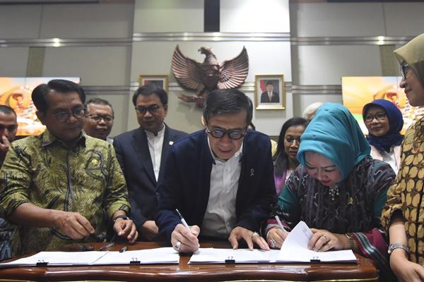 Menteri Hukum dan HAM Yasonna Laoly saat menandatangani draft kesepakatan RUU Pemasyarakatan dengan perwakilan fraksi-fraksi saat Rapat Kerja dengan Komisi III DPR di Kompleks Parlemen, Senayan, Jakarta, Selasa (17/9/2019). - ANTARA/Indrianto Eko Suwarso