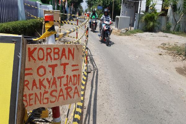 Pengendara motor melintas di dekat lubang proyek Saluran Air Hujan yang mangkrak, di Jalan Babaran, Rabu (28/8/2019). - Harian Jogja/Lugas Subarkah