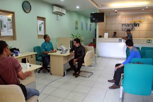 Ilustrasi-Nasabah melakukan transaksi di Bank Mandiri Syariah Palu, Sulawesi Tengah, Kamis (4/10/2018). - JIBI/Paulus Tandi Bone