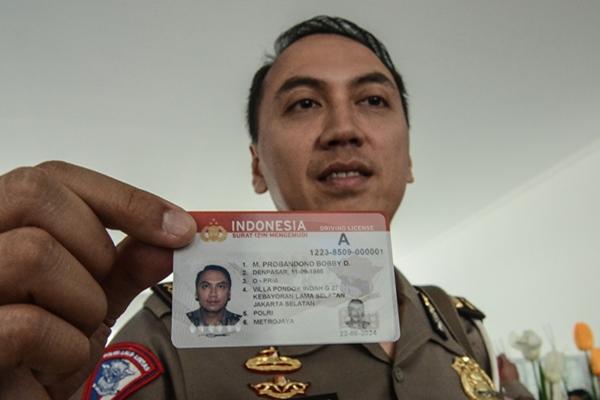 Polisi menunjukkan kartu Smart SIM (Surat Izin Mengemudi) di Gedung Satuan Penyelenggara Administrasi (Satpas) dan gerai SIM di Kabupaten Bekasi, Cikarang, Jawa Barat, Kamis (22/8/2019). Kartu Smart SIM berfungsi sebagai alat pembayaran e-tilang, jalan tol dan transportasi umum dengan saldo maksimal Rp 2 juta - ANTARA FOTO/Fakhri Hermansyah