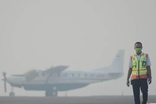 Ilustrasi-Petugas Apron Movement Control (AMC) Bandara Sultan Thaha Jambi mengecek kondisi landasan saat kabut asap menyelimuti kota itu. - Antara