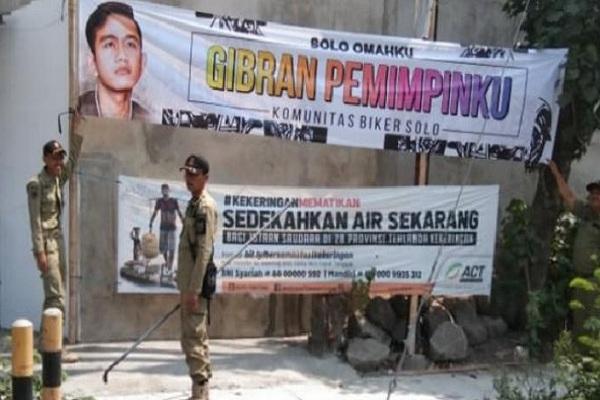 Sejumlah petugas Satpol PP Surakarta menertibkan spanduk bergambar Gibran Rakabuming Raka. - Antara