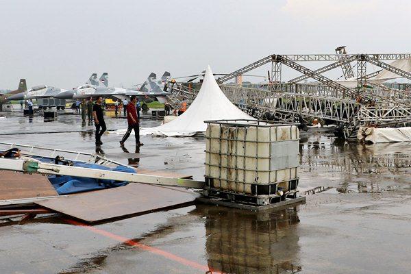 Pengunjung berjalan di sekitar tenda yang rusak pascaterjangan kencang di areal Pameran Dirgantara 2017 di Terminal Selatan, Lanud Halim Perdanakusuma, Jakarta, Jumat (21/4). - Antara/Ricky Aldhian Mukhlis