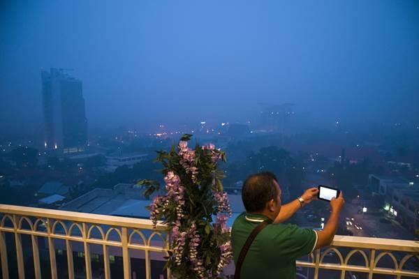 Asap menyelimuti Kota Pekanbaru, Riau, pada Senin malam (28/9). - Antara