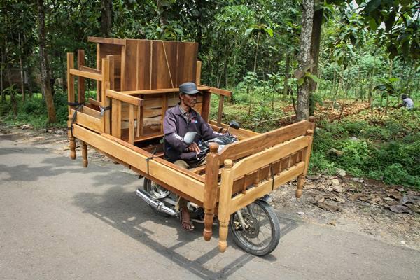Perajin mebel mengantarkan mebel kayu menggunakan sepeda motor di kawasan Kalijambe, Sragen, Jawa Tengah, Senin (6/3). Kementerian Lingkungan Hidup dan Kehutanan (KLHK) berharap industri mebel atau kerajinan kayu dipermudah dalam kepengurusan sertifikat Forest Stewardship Council (FSC), meskipun telah ada sertifikat Sistem Verifikasi Legalitas Kayu (SVLK) untuk mempermudah ekspor produknya. - Antara