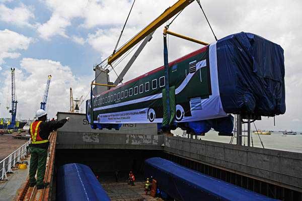 Suasana proses pemuatan gerbong kereta produksi PT INKA tipe 'Broad Gauge' ke dalam lumbung kapal untuk dikirim ke Bangladesh, di Pelabuhan Tanjung Perak, Surabaya, Jawa Timur, Minggu (20/1/2019). - ANTARA/Zabur Karuru