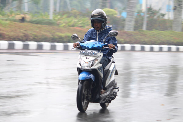 Pengendara sepeda motor melintasi Jalan Rahadi Oesman yang basah setelah hujan turun, di Pontianak, Kalimantan Barat, Senin (23/9/2019). Walau hujan sudah mengguyur Kota Pontianak pada Senin (23/9/2019) subuh hingga pagi hari namun kabut asap masih menyelimuti kota tersebut. - Antara/Jessica Helena Wuysang