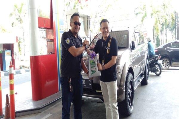 General Manager Pertamina MOR IV Iin Febrian (kanan) saat melakukan bagi-bagi oli gratis pada salah satu SPBU di Semarang. - Bisnis/Alif Nazzala R.s