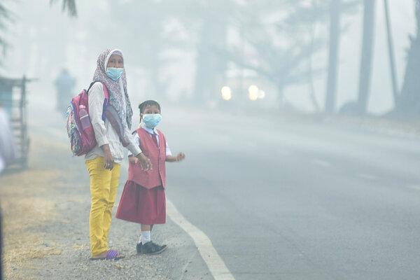 Seorang siswa bersama orang tuanya mengenakan masker saat menunggu angkutan umum, di Palembang, Sumatera Selatan, Senin (23/9/2019). Pemerintah Kota Palembang meliburkan siswa sekolah selama tiga hari, 23-25 September 2019 akibat asap yang dapat membahayakan kesehatan. - Antara/Mushaful Imam