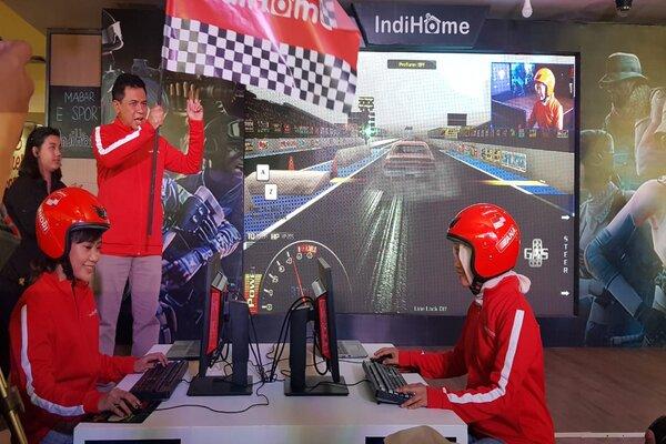 Deputi VP Marketing Telkom Regional V Jatim Bali Nus, Muhamad Khamdan (memegang bendera), dan Direktur Consumer Service Telkom Siti Choiriana (kanan mengenakan helm) saat mencoba bermain game dengan menggunakan IndiHome 300 Mbps dalam Re-Launching IndiHome 200 Mbps dan 300 Mbps di Surabaya, Senin (23/9/2019). - Bisnis/Peni Widarti