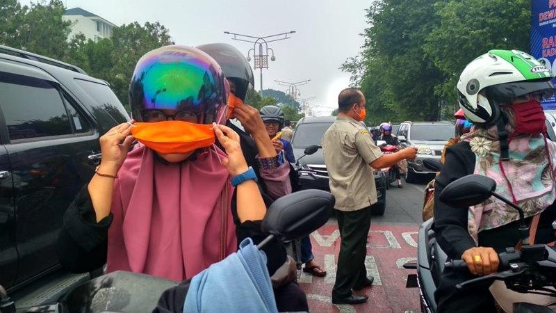 Pengendara memakai masker yang dibagikan anggota Badan Penanggulangan Bencana Daerah Aceh di Simpang Lima, Banda Aceh, Senin (23/9/2019). Hari ini, BPBD Aceh bersama  Kodim 0101 - BS, Polresta Banda Aceh dan Forum Pengurangan Risiko Bencana Aceh membagikan sekitar 10 ribu masker kepada pengguna jalan.
