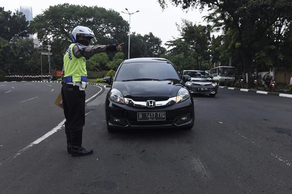 Polisi memberhentikan mobil berplat nomor ganjil yang melintas pada tanggal genap di kawasan pembatasan lalu lintas ganjil-genap di sekitar Bundaran Senayan, Jakarta, Selasa (30/8). - Antara