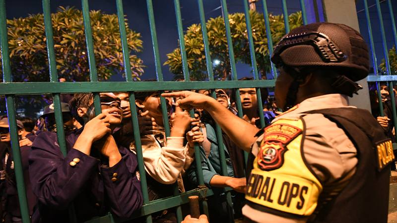 Seorang Polisi berbincang dengan massa mahasiswa yang berunjuk rasa di depan kompleks Parlemen, Jakarta, Senin (23/9/2019) malam. Ribuan mahasiswa yang berasal dari kampus se-Jabodetabek turun ke jalan berdemonstrasi menolak UU KPK dan pengesahan RUU KUHP. - Antara