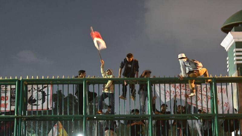 Massa mahasiswa berusaha memanjat pagar saat berunjuk rasa di depan kompleks Parlemen, Jakarta, Senin (23/9/2019) malam. Ribuan mahasiswa yang berasal dari kampus se-Jabodetabek turun ke jalan berdemonstrasi menolak UU KPK dan pengesahan RUU KUHP.  - Antara