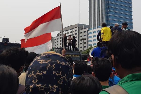 Kapolres Jakarta Pusat Kombes Harry Kurniawan berdiri di atap mobil taktis polisi saat berdialog dengan mahasiswa pengunjuk rasa  di depan Gedung DPR pada Selasa 24 September 2019. - Bisnis/Feni Freycinetia