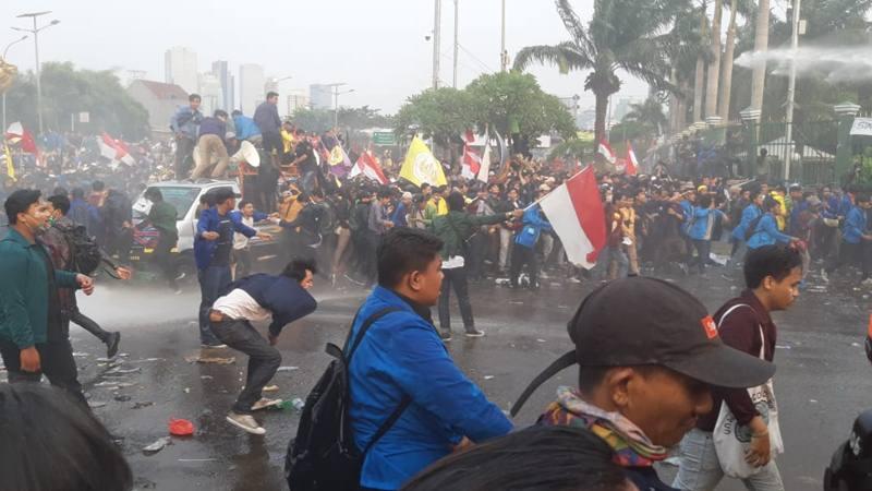 Polisi menembakan gas air mata ke mahasiswa yang menggelar aksi demonstrasi di depan gedung DPR/MPR, Selasa (24/9). - Bisnis/Rayful Mudassir