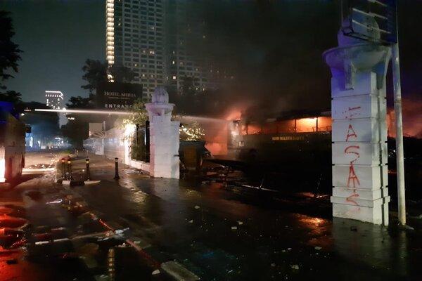 Water cannon polisi memadamkan bus yang dibakar. - Bisnis