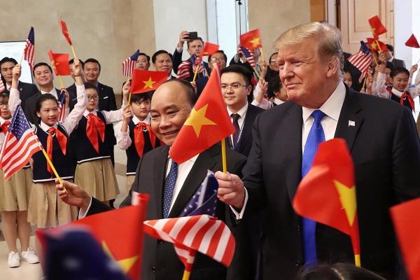 Presiden AS Donald Trump (kanan) dan Perdana Menteri (PM) Vietnam Nguyen Xuan Phuc melambaikan bendera Vietnam sambil menyapa para siswa yang menyambut mereka di Hanoi, Vietnam, Rabu (27/2/2019). - Reuters/Leah Millis