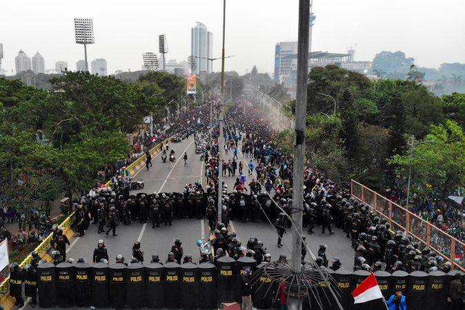 Mahasiswa bentrok dengan aparat kepolisian saat aksi unjuk rasa di depan Gedung DPR, Jakarta, (24/9). Bentrokan terjadi saat polisi berusaha membubarkan aksi mahasiswa yang menolak revisi sejumlah Undang-undang yang diusulkan DPR. - Bisnis/Abdullah Azzam