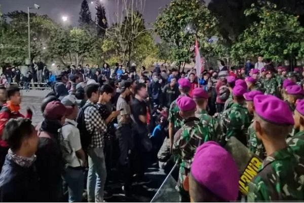 Mahasiswa bercengkerama dengan sejumlah prajurit TNI AD dan Marinir yang berjaga di bawah jembatan layang Jakarta Convention Center, Senayan, Jakarta, Selasa (24/9/2019). - Antara