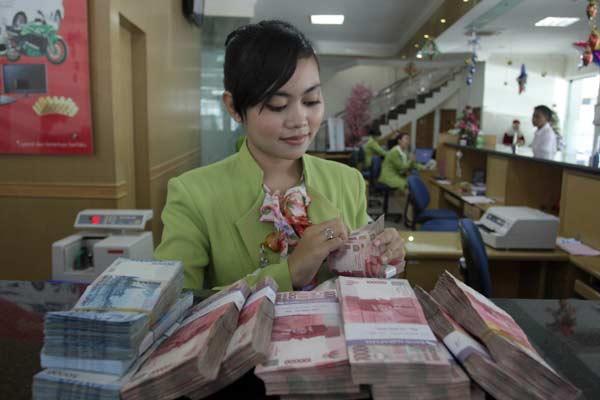 Ilustrasi BPR. Kasir Bank Perkreditan Rakyat (BPR) menghitung uang rupiah.  - Bisnis.com